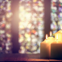 Candles burning in a church background